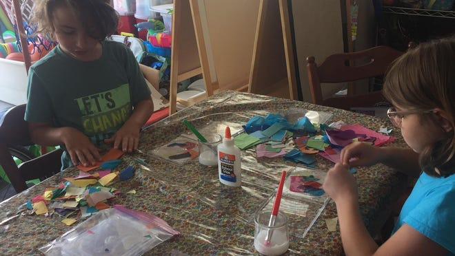 Siblings Mitchell Rucinksi, 7, and Annabelle Rucinksi, 10, work on art projects from an Ohio Craft Museum box. The craft museum provides the boxes weekly to fill in for summer kids' camps that have been canceled because of the pandemic.
