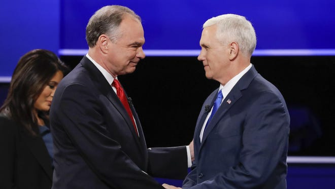 Republican vice-presidential nominee Gov. Mike Pence, right, and Democratic vice-presidential nominee Sen. Tim Kaine shake hands during the vice-presidential debate Tuesday at Longwood University in Farmville, Virginia.