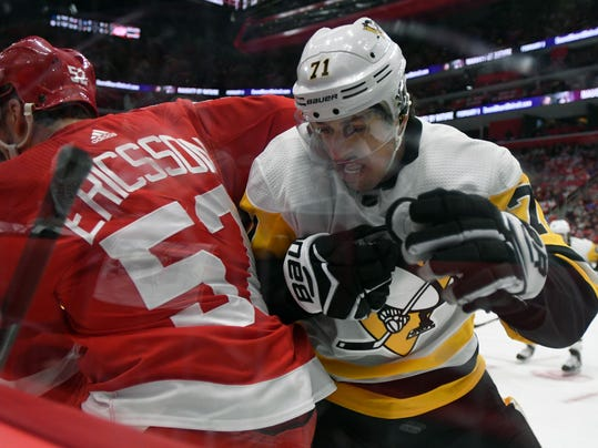 Detroit Red Wings defenseman Jonathan Ericsson (52), of Sweden, is hit from behind by Pittsburgh Penguins center Evgeni Malkin (71), of Russia, during the first period of an NHL hockey game in Detroit, Sunday, Dec. 31, 2017. (AP Photo/Jose Juarez)