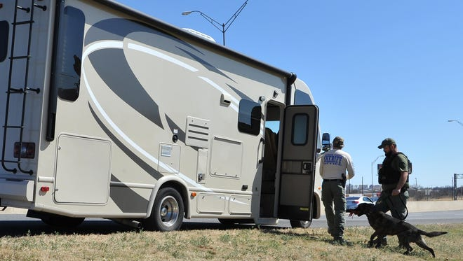 A Wichita County Sheriff's deputy and his K-9 partner search a recreational vehicle Friday afternoon on Central Freeway near the Maurine Street exit.