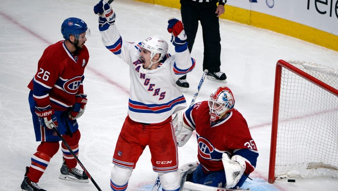 New York Rangers forward Chris Kreider (20) reacts after the goal scored by teammate Martin St-Louis (not pictured) against Montreal Canadiens goalie Dustin Tokarski (35) and Josh Gorges (26) during the second period in game two of the Eastern Conference Final of the 2014 Stanley Cup Playoffs at the Bell Centre.