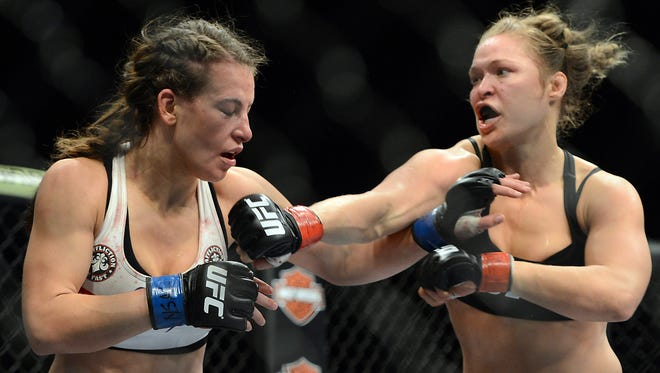 Ronda Rousey, right, throws a right hand at Miesha Tate during their UFC women's bantamweight championship bout at the MGM Grand Garden Arena in December. Rousey won by armbar.