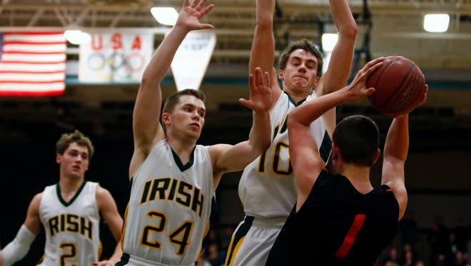 Logan Maulick (24) and Brett Schommer of Freedom seal off Bennett Vander Plas of Ripon during an Eastern Valley Conference boys' basketball game at Freedom on Jan. 6.