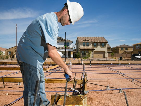 Construction worker Neal Boatman works on a home in the mixed-use Eastmark community in Mesa. The community has been praised for the flexible collaboration between DMB Associates and the city.