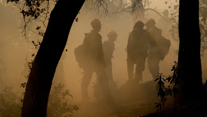 Firefighters from Kern County work to put out hot spots from the Thomas Fire on Saturday in Montecito.