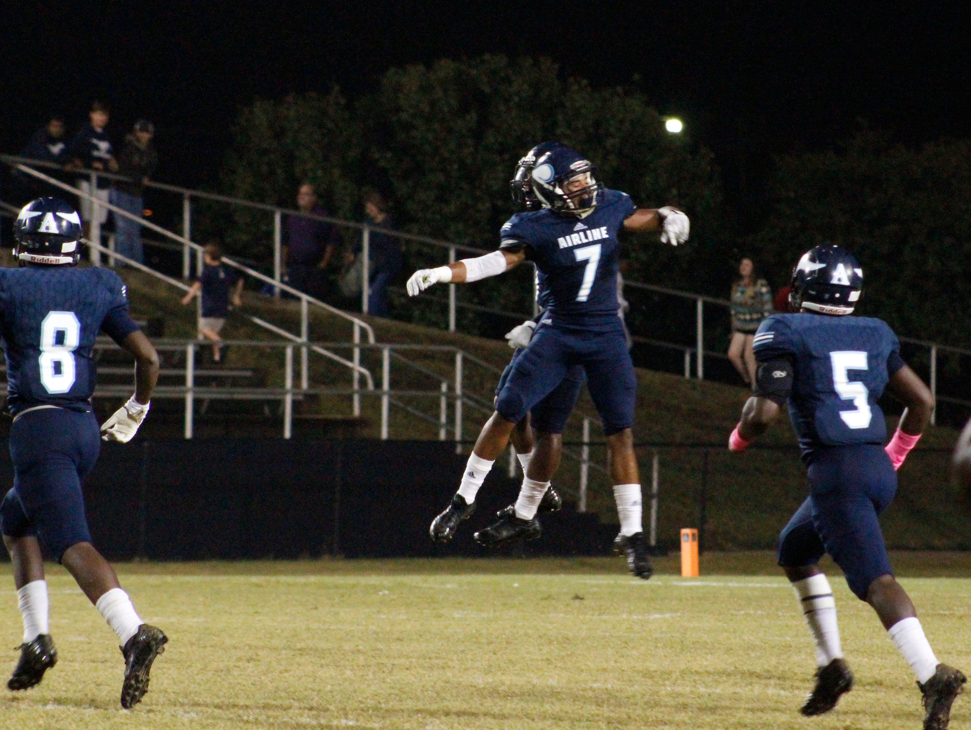 The Airline High School Vikings jump to celebrate after scoring a touchdown against the Haughton High School Buccaneers on Friday night in Bossier City.