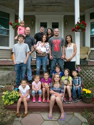 Tanya Klepps' family, from left, bottom row: Ayriani Swiedarke, 6, Evelyn Swiedarke, 3, Ava Swiedarke, 7, Sophia Klepps, 7, Abigail Klepps, 12, Isiabella Klepps, 9, Ayce Hoerter, 6. From left, middle row: Nicholas Klepps, 15, Brittany Swiedarke, Natalia Swiedarke, 2 months, Anthony Hoerter, Pachee Hoerter. From left, back row: Rylee Swiedarke, 1, Jake Swiedarke, Joe Kleeps, and Tanya Kleeps pose in front of the Klepps' home in Stevens Point, Friday, May 8, 2015. Not pictured: Alec Klepps, 24, Tristan Klepps, 19, Conner Klepps, 17, Beau Rosenthal, 16, and Chyaine Rosenthal, 20.