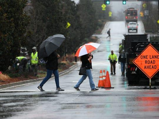 UT students walking to class across Volunteer Blvd in heavy rain Thursday, Mar. 1, 2018.