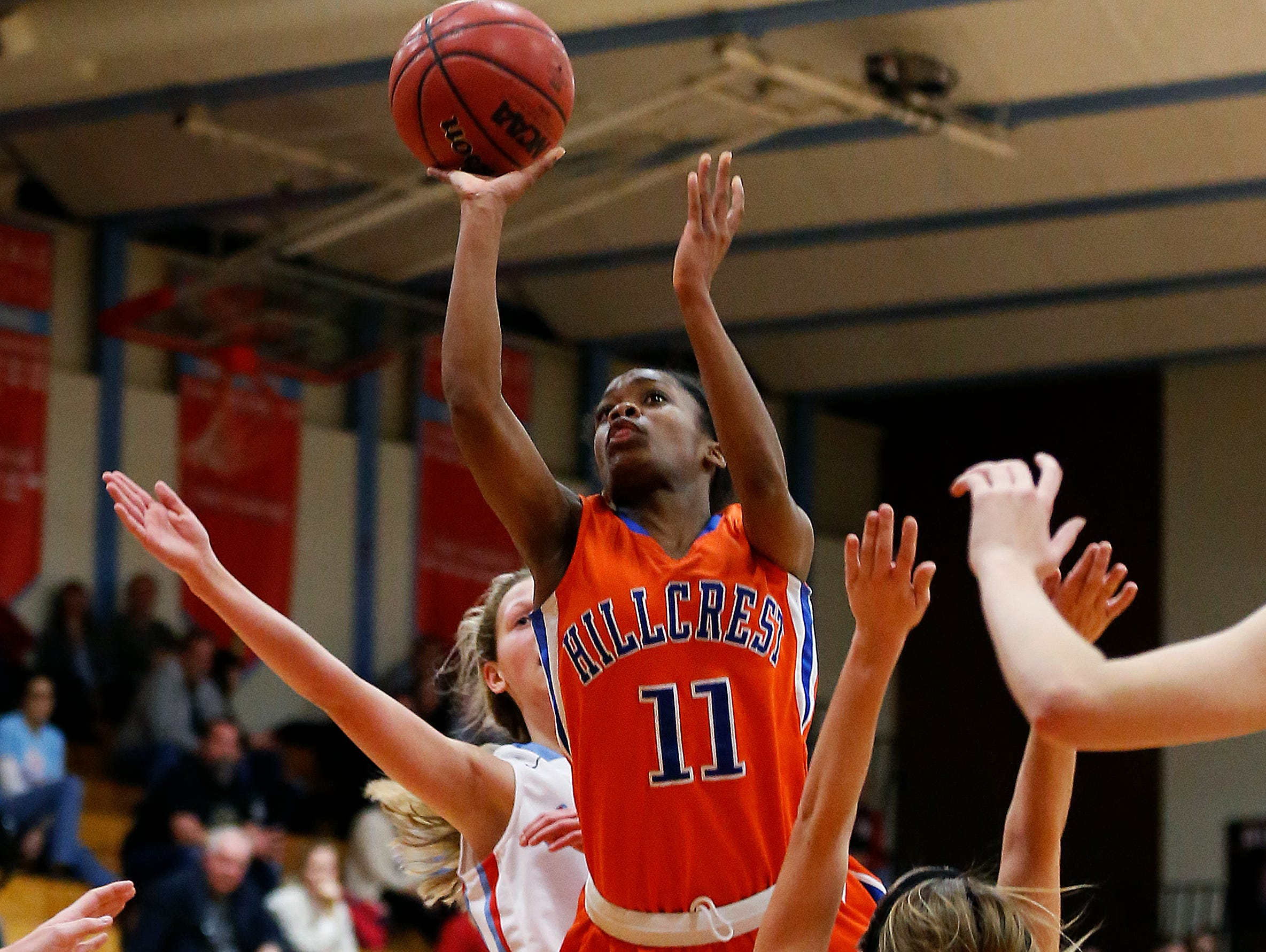 Hillcrest High School senior Kaycee Gerald (11) shoots between two Falcons defenders during third quarter action of the Hornets' game against Glendale High School at Glendale High School in Springfield, Mo. on Jan. 7, 2015. The Hornets won the game 49-39.