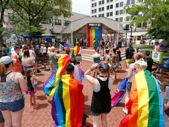 Greater Ozarks Pridefest 2017 attendees dance and sing as they listen to a band play on Saturday, June 17, 2017.