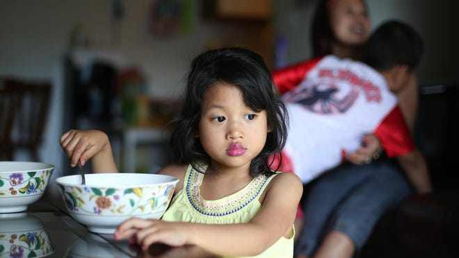 Sui Hlei Cuai gets a surprise hug from her son as her daughter eats a bowl of cereal.