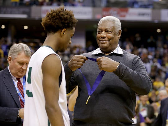 Oscar Robertson looks to put the winning medal around Crispus Attucks Tigers Jamal Harris (5) after winning the IHSAA 3A Boys Basketball State Finals game Saturday, March 25, 2017, evening at Bankers Life Fieldhouse. The Crispus Attucks Tigers defeated the Twin Lakes Indians 73-71.