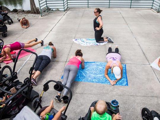 Jennifer Garner, center, helps lead a group in planks