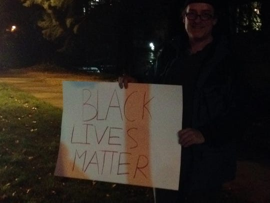 Stan Trumpi holds a sign at a protest at the Salem