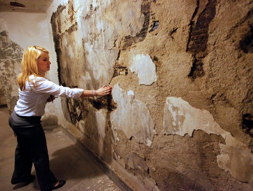 Jenna Stoll, marketing coordinator, examines water damage along a wall on the third floor of the Museum Center on the backside of the rotunda.