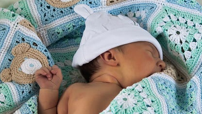 New born baby son on the handmade blue blanket