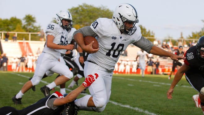 East Lansing's Connor Charamella (10) is brought down by St. Johns' Carson VanDeberg Friday, Aug. 25, 2017, in St. Johns, Mich.