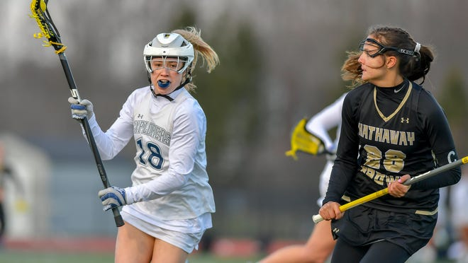 Mia Becker, left, has possession of the ball against Hathaway Brown last year. Becker recently decided to continue her academic and lacrosse careers at the United States Coast Guard Academy in New London, Connecticut.
