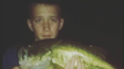 Cameron MacKnett holds a bass he caught while night