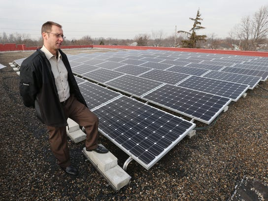 Joe Bowling looks over solar panels on the roof of the Englewood Christian Church in 2015.