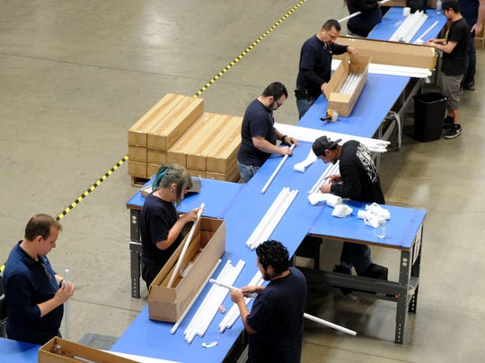 A group of employees from Revolution Lighting work on LED tubes inside the warehouse in Simi Valley. The company creates energy-efficient lighting products.