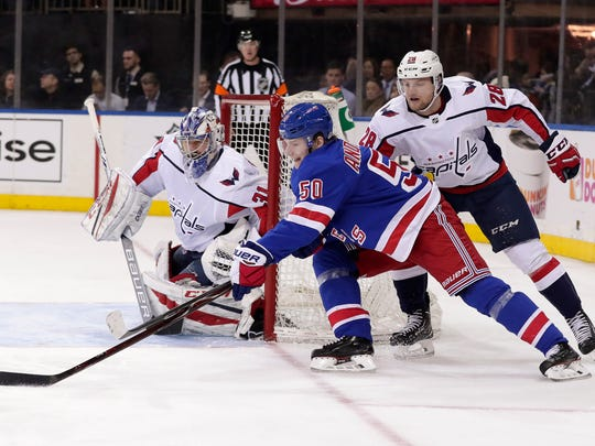 New York Rangers center Lias Andersson (50) tries to wrap the puck around the goal against Washington Capitals goaltender Philipp Grubauer (31) and defenseman Jakub Jerabek (28) during the second period of an NHL hockey game, Monday, March 26, 2018, in New York. (AP Photo/Julie Jacobson)