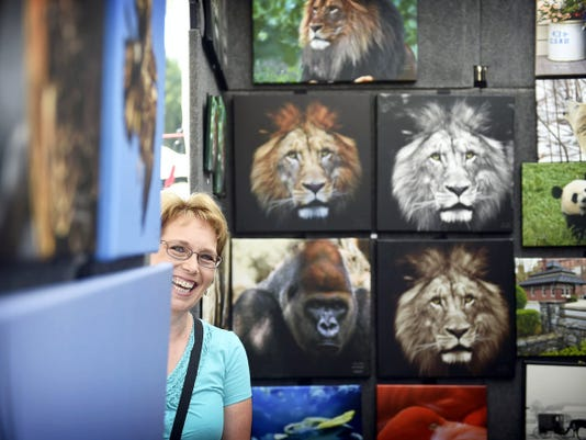 Sharon Smith of Logos Photography of Lititz greets guests to her tent at the Mt. Gretna Outdoor Craft Show Saturday. The craft show is held in conjunction with the 41st Annual Mt. Gretna Outdoor Art Show. Thousands packed the center of the town to view and buy art from dozens of vendors.