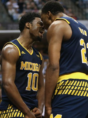 Michigan Wolverines' Derrick Walton Jr. and Zak Irvin celebrate after a basket against the Purdue Boilermakers during second half action on Saturday, March 12, 2016 at Bankers Life Fieldhouse in Indianapolis.