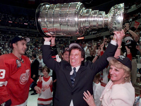 Mike Ilitch, center, hoists the Stanley Cup in June