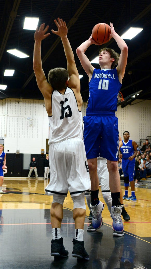 McDowell's Cannon Lamb goes up for a shot against North Buncombe's Jack Ritchie during their game at North Buncombe High School on Friday, Dec. 16, 2016. The Titans defeated the Blackhawks 87-73.