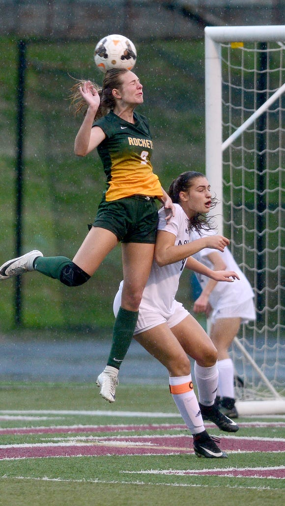 Reynolds' Addie Porter heads the ball over Asheville's Liz Tsiros during their game at Asheville High School on Tuesday, April 24, 2018. The teams tied 2-2 in overtime.