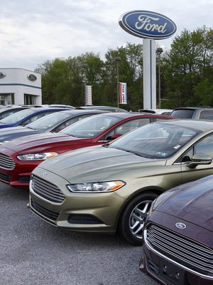 Cars are seen at an automobile dealer in Zelienople, Pa.