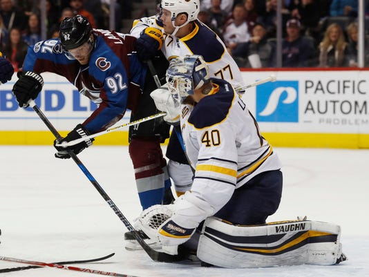 Colorado Avalanche left wing Gabriel Landeskog, left, of Sweden, directs a shot past Buffalo Sabres defenseman Dmitry Kulikov, of Russia, as goalie Robin Lehner, also of Sweden, stops the puck in the first period of an NHL hockey game Saturday, Feb. 25, 2017, in Denver. (AP Photo/David Zalubowski)