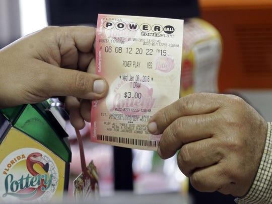 A clerk hands over a Powerball ticket to a customer Wednesday at a local grocery store in Hialeah, Fla.