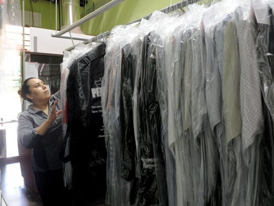 Viridiana Hernandez, a clerk at Persnickity Dry Cleaners in Ventura, starts putting clothes in order.