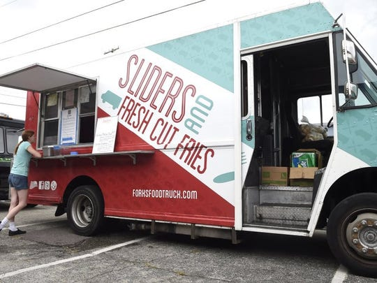 A worker prepares to open the Forks on the Road food truck parked along E. Depot Ave. in the Magnolia Ave. Warehouse District on Thursday, Aug. 6, 2015. (ADAM LAU/NEWS SENTINEL)