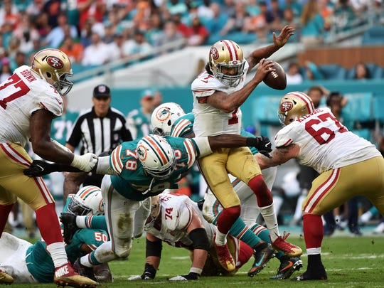 Miami Dolphins defensive end Terrence Fede, center, swoops in to tackle San Francisco 49ers quarterback Colin Kaepernick at Hard Rock Stadium on Nov. 27 in Miami Gardens, Florida.