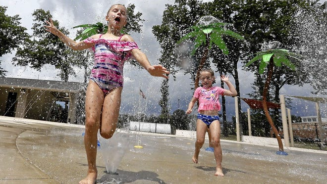 Chloe Needham, 7, and her sister Emma, 4, both of Whitehall, run through the splash pad July 10 at John Bishop Park in Whitehall. The sisters were with their mom, April Kantor. The splash pad has opened for the summer, though appointments for specific, 90-minute time slots must be made in advance.