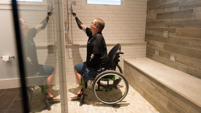 Christopher Walker shows his new handicap accessible shower his new home in Alexandria, VA  July 7, 2017.