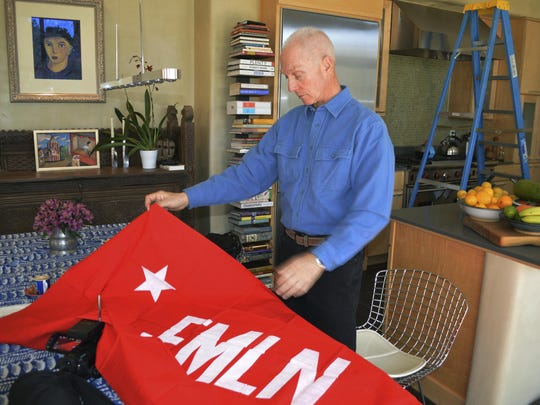 "In this Jan. 17, 2019 photo, Todd Greentree, a former U.S. Embassy political officer in El Salvador during its civil war, shows a rebel Farabundo Marti National Liberation Front flag in his Santa Fe, N.M., home as he talks about the killings of four Dutch journalists in 1982. Greentree said that he's ""very ambivalent"" about seeking justice for what he called an obvious war crime."
