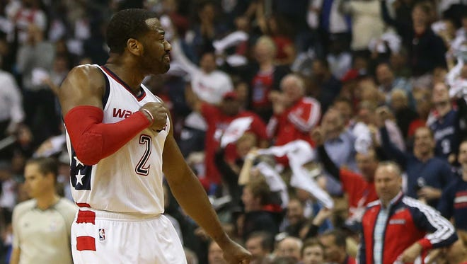 Washington Wizards guard John Wall (2) reacts after making a three-point field goal against the Atlanta Hawks in the first quarter in Game 2 of the first round of the 2017 NBA Playoffs at Verizon Center.