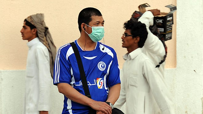 A foreign worker living in Riyadh, Saudi Arabia, wears a mask covering his mouth and nose on a main street in the Saudi capital April 29 as the death toll from the newly emerged and often fatal Middle East Respiratory Syndrome (MERS) disease topped 100 in the desert kingdom.