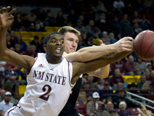 New Mexico State guard Braxton Huggins fights for the
