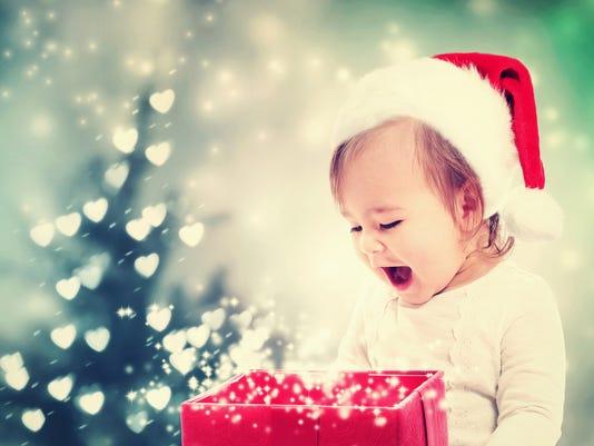 Happy Toddler girl looking at Christmas present box