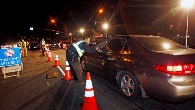In this Dec. 16, 2011 photo, police officers check drivers at a sobriety checkpoint in Escondido, Calif.
