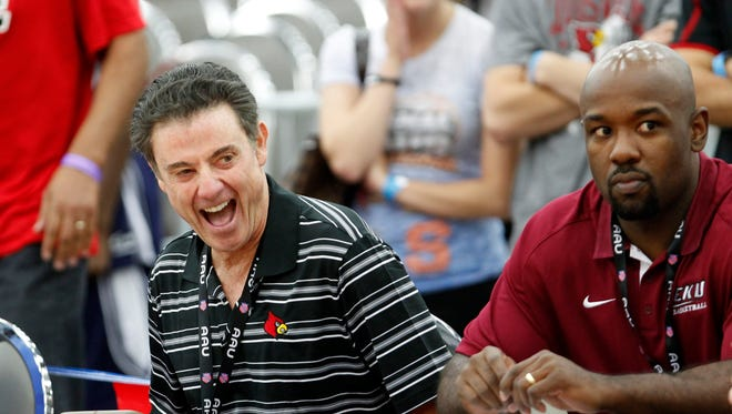 University of Louisville head basketball coach Rick Pitino shares a laugh with other coaches as they watch games at the AAU basketball Championship at the Fairgrounds in Louisville, Kentucky.       July 24, 2014