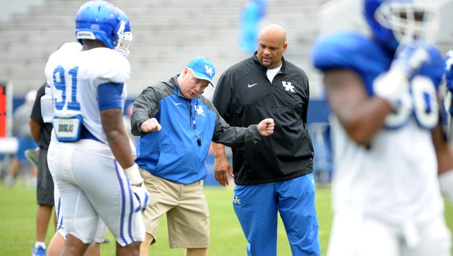 Head coach mark Stoops instructs defensive linemen as defensive line coach Jimmy Brumbaugh watches during the University of Kentucky football fan day at Commonwealth Stadium in Lexington, KY. Saturday, August 9, 2014.