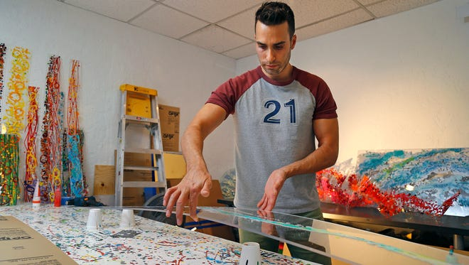 Artist Rocco Menaguale works on a piece for an upcoming show at his studio on July 1, 2014, in Phoenix.