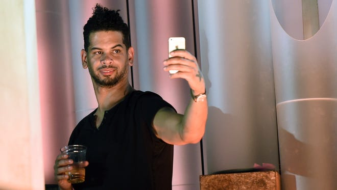 DJ/producer Marc Kinchen takes images of fans on a cell phone from the side of the stage after he performed at the 18th annual Electric Daisy Carnival at Las Vegas Motor Speedway on June 21, 2014, in Las Vegas, Nev.