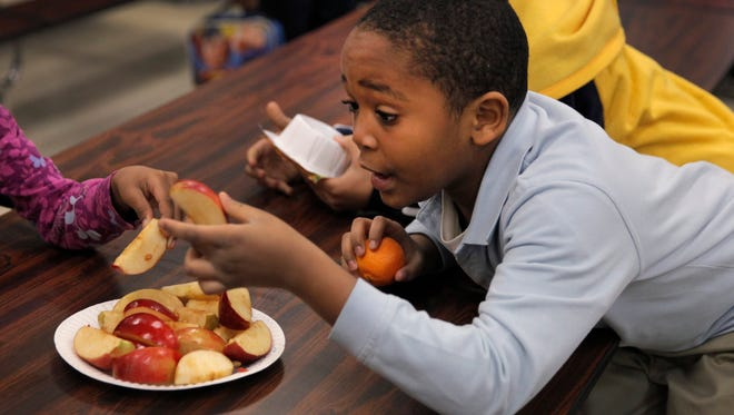 Second-grader Jesse Tucker, age 8, tastes some Ida Red apples at School 12 in the city during a lunch period in 2012. The students tasted several varieties of apples to see which ones they liked the best, part of a program to introduce healthy choices in students' lives.